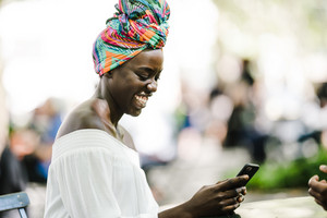 happy black woman on mobile device