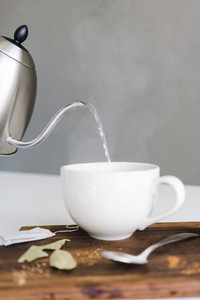 kettle of water pouring into a tea cup