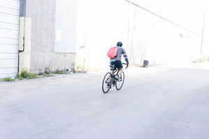 man bikes down the road with helmet on