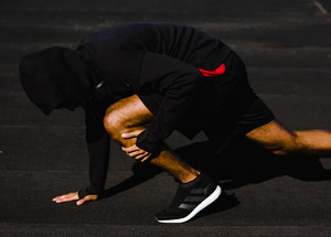 man does leg stretches in athletic clothes