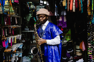 Man holding a saxophone in front of a storefront in the village