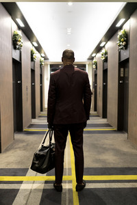 man in a suit approaches the hotel elevators with a duffle bag