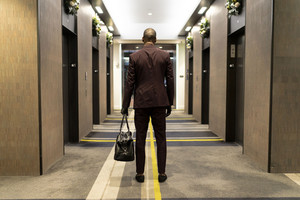 man in a suit walks towards hotel elevators with a duffle bag