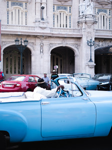 man in fidora driving blue vitntage convertible
