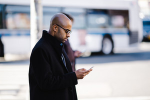 man in heavy coat looks down at his cell phone
