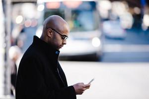 man in heavy coat scrolls down phone outside
