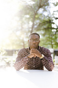 man in thin round glasses button wearing a down shirt with patterns at a table outside