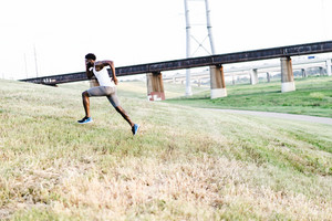 man in workout clothes running up a slight hill