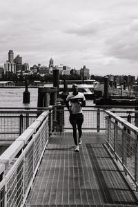 man jogs around a harbor