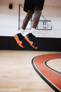 man jumping high in the air with basketball shoes