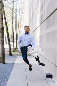 man jumps outside in formal clothing