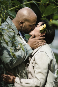 man kisses a woman with a sunflower on her ear