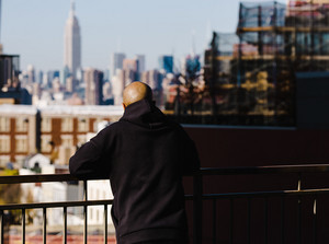 man looks out at city view