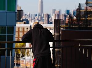 man looks over balcony
