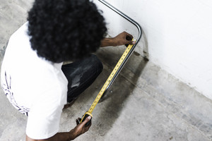 man near wall using a measuring tape