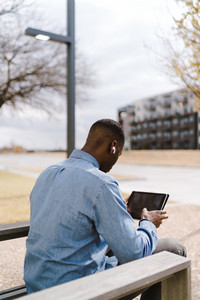 man on a tablet sits outside