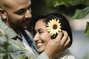 man puts a sunflower in woman's ear