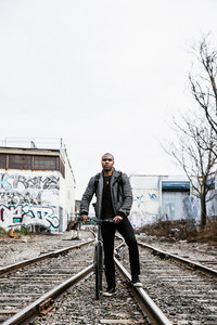 man rides his bicycle on train tracks surrounded by graffiti