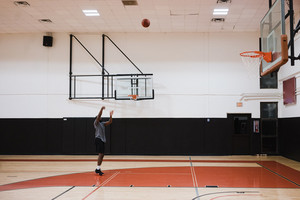 man shoots basketball from the freethrow line