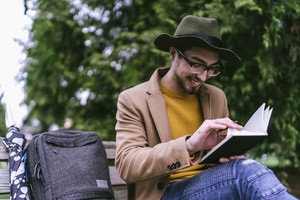 man sitting outside and smiling while writing in journal with backpack and umbrella