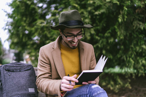 man sitting outside and smiling while writing in journal with backpack