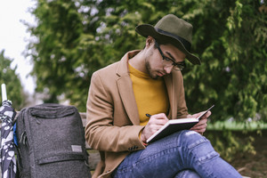 man sitting outside and writing in journal with backpack and umbrella
