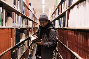 man standing in front of a library shelf reading a book