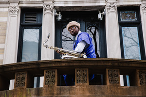 man standing outside of historic building with a saxophone