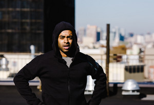 man standing with a hoodie on  tired after workout