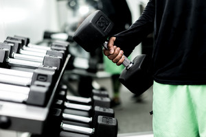 man takes weights off rack in gym