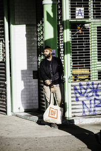 man waiting outside with grocery bag