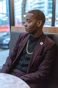 man wearing a maroon suit wearing a gold chain sitting in a booth