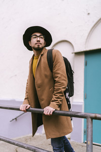 man wearing glasses hat and coat and backpack while leaning against railing