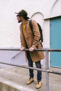 man wearing glasses hat and coat while leaning against railing