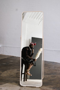 man wearing nigerian clothing sitting on a stool looking through a mirror