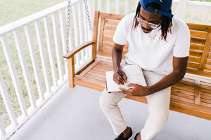 man with black and brown dreads sits outside to read