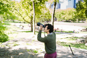 man with dark curly hair wearing green sweater and purple pants taking photo of nature