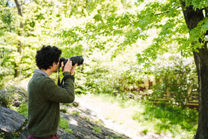 man with dark curly hair wearing green sweater taking photo of nature