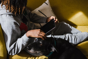 man with dreads on a yellow couch with his iPad