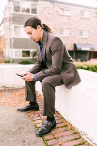 Man with hair pulled back glances at his phone