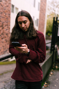 Man with long hair looks at his phone