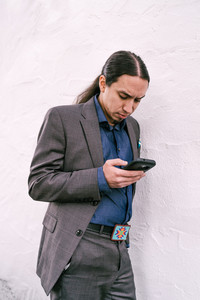 Man with long hair pulled back on his phone outside