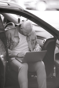 man works on his tablet in car