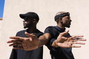 men in black pose together outside