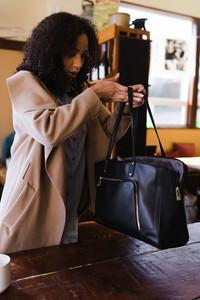 Mixed race woman lifting up her bag