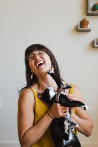 Mixed race woman playing with cat
