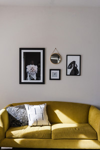 mustard colored couch with black and white pictures and mirror hanging above