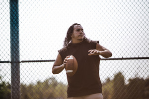 native american man ready to throw football in the air