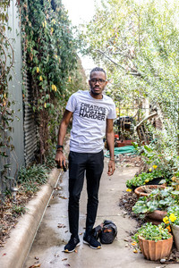 Nigerian man standing outside with plants