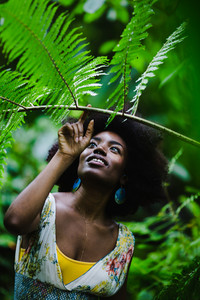 nigerian woman admires branch in the rain forest